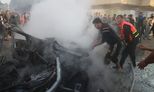 A Palestinian firefighter extinguishes a fire after what witnesses said was an Israeli air strike on a car in Gaza City