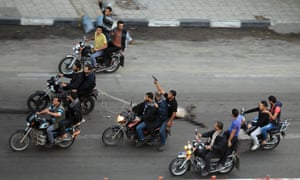 Palestinian gunmen ride motorcycles as they drag the body of a man, who was suspected of working for Israel, in Gaza City November 20, 2012.