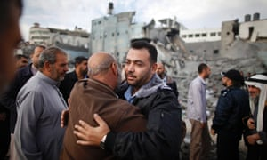 A Hamas police officer is hugged by a Palestinian man after they returned to their destroyed police headquarters on Thursday.