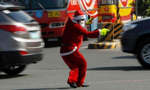 Ramiro Hinojas, 47, a traffic enforcer, wears a Santa Claus costume as he directs traffic along a main street in Pasay city, Manila, the Philippines.