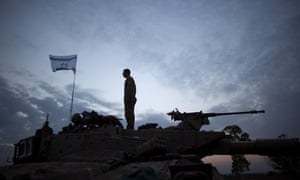 An Israeli soldier stands on his tank in a deployment area on Israel's border with the Gaza Strip.The ceasefire between Israel and Hamas appears to be holding  War.