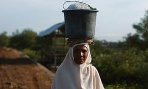 A woman carries a bucket of salt on her head in Palibelo village, on the outskirts of Bima, on Indonesia's Sumbawa island.