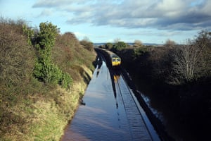 Flooding in UK: A train waits to pass along flooded track, Taunton