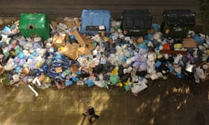A pedestrian walks past a pile of uncollected rubbish during the 21st day of the refuse collectors' strike in Jerez de la Frontera, Spain.