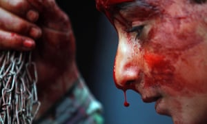 Blood drips from the nose of a Kashmiri Muslim boy as he flagellates his head during a Muharram procession in Srinagar, India.