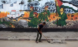 A Palestinian worker cleans the street in front of graffiti near the destroyed Al-Saraya Hamas headquarters in Gaza City.