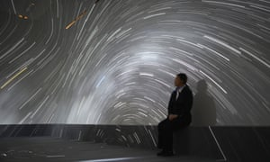 A young Japanese woman looks at stars displayed during the 'Star Cruise Planetarium' at Roppongi Hills in Tokyo, Japan.