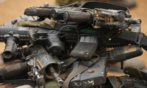 Israeli soldiers' assault rifles lie piled on the ground.