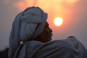Camel fair: A camel trader sits in a field at sunset at the fair
