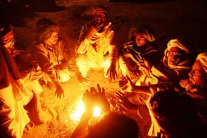 Camel fair: Camel traders sit around a fire before dawn