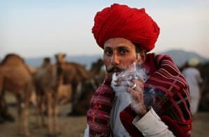 Camel fair: An Indian camel herder smokes a cigarette