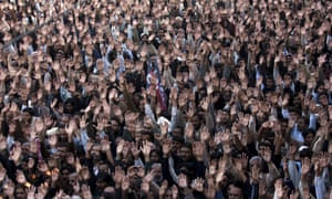 People raise their hands to condemn a suicide attack on Shiite mourners during a funeral in Rawalpindi, Pakistan. A Taliban suicide bomber struck a Shiite Muslim procession near Pakistan's capital, killing nearly two dozen people in the latest of a series of bombings targeting Shiites.