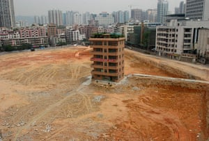 China demolition: A house stands isolated in the middle of a construction site