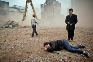 China demolition: A woman who tried to protect her house being demolished cries