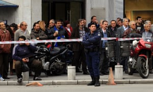 People watch a police operation at the Deposits and Loans Fund bank where an armed elderly man threatened to set himself on fire in the northern Greek port city of Thessaloniki.