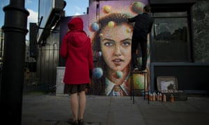 A passerby watches Australian artist James Cochran