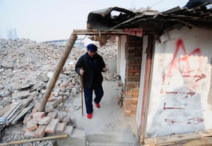 China demolition: Cao Wenxia, 75, the owner of a nail house, walks out of his house in Hefei