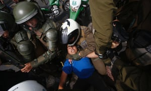 A student protester is held down by riot policemen in Santiago while taking part in a rally