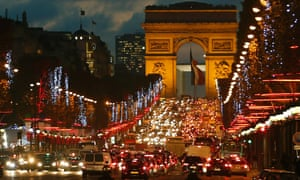 Christmas lights hang from trees along the Champs Elysees as the rush hour traffic fills the avenue leading up to the Arc de Triomphe in Paris.