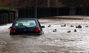 Ducks swim near to a car that was stranded in floodwater in Evesham, Worcestershire.