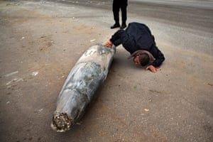 Bernat Armangue: A Hamas officer inspects an unexploded Israeli missile in Gaza City