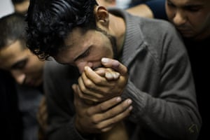 Bernat Armangue: A Palestinian man kisses the hand of a dead relative in Shifa Hospital