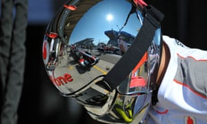 One of the cars of McLaren Formula One team is reflected on the helmet of a mechanic as he gets ready to change the tyres.