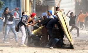 Egyptian protesters take cover from tear gas during clashes with police forces in Mohamed Mahmoud street near Tahrir Square on Thursday. Clashes erupted late Monday between police and protesters who were marking the first anniversary of deadly clashes in the street.