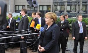 German Chancellor Angela Merkel talks to the press as she arrives at the EU headquarters