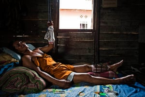 Tin Mining: Suge, a sea tin miner, lying in bed at his home in Belo Laut Village