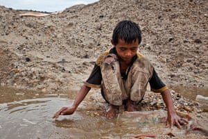 Tin Mining: Febri Andika, a child tin miner, searching for tin ore in Belo Laut Village
