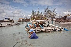 Tin Mining: Edi, a sea tin miner, uses a bamboo raft to dredge for tin ore