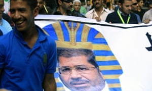 Egyptian protesters hold a banner depicting Egyptian President Mohamed Morsi as a Pharaoh, during a rally in Cairo against his decision to grant himself sweeping new powers.