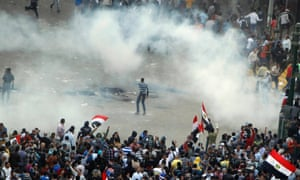 Protesters run from tear gas released by riot police during clashes at Tahrir square in Cairo.