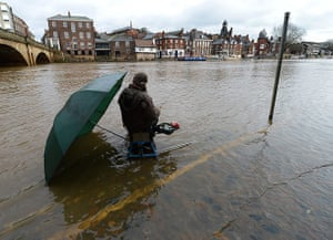 UK flooding: A fisherman takes advantage of the rising floodwater from River Ouse, York
