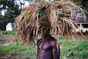 FTA: Joe Penney: A farmer carrying wheat on his head poses as he walks home