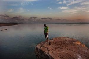 FTA: Joe Penney: Student Rachid Malam peers off the edge of a colonial-era dock, Bolama