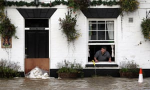 David Boazman, landlord of the White Bear Pub in Tewkesbury looks out of the window as he pumps water from the pub.
