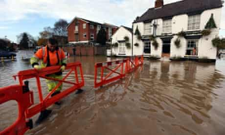A highways agency worker barriers off the road outside the White Bear Pub in Tewkesbury to stop motorists driving through flood water and flooding the pub further.