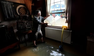 And this why. David Boazman throws water out of the bar window of his flooded pub.