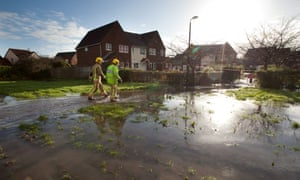 Firefighters walk through flood water as they install water pumps to try save houses from flood waters after flash flooding hit the village of Worle, Somerset.