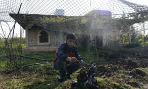 A Syrian boy picks up parts of explosive devices that landed on his front garden in the village of Atme, near the Turkish border in Syria's Idlib province.