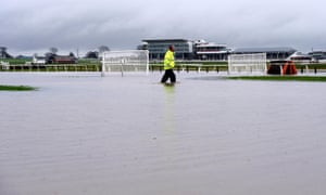 Head Groundsman Ian Ward wades through floodwater on the track following torrential rain at Wetherby Racecourse, Yorkshire.