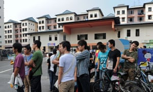 Foreign workers wait for their transport to work outside their dormitory in Singapore.  More than 100 mainland Chinese bus drivers in Singapore refused to work in a rare strike in the city-state.