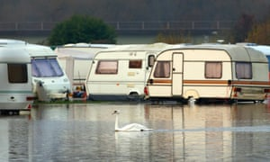 A swan swims through flood waters from the River Soar at a caravan park in Barrow Upon Soar.