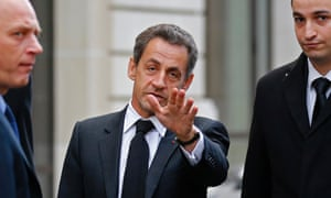 Former French President Nicolas Sarkozy reacts as he leaves his car in Paris after a lunch meeting with his former Prime Minister Francois Fillon to discuss the UMP political party's crisis.
