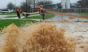 Firefighters prepare to pump water away from a beck behind the Friarage Hospital in Northallerton, North Yorkshire as the heavy rain continues across the UK.