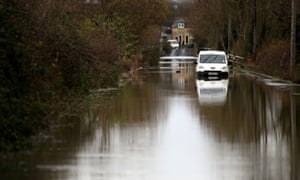 A white van is left abandoned on a country lane as flood waters from the River Nene close a road in Ringstead, Northamptonshire.