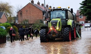 Schoolchildren trudge through floodwaters as they make their way past a tractor down a flooded street in Northallerton, North Yorkshire.
