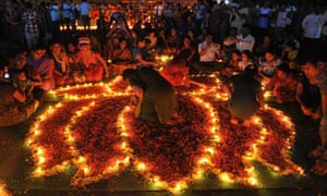 Indian Hindu devotees perform a ritual by lighting diyas - earthen lamps - on the occasion of Karthika month in Hyderabad.